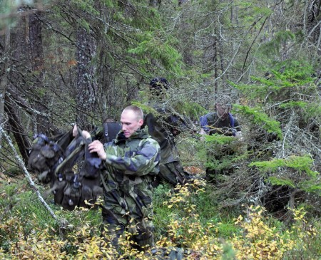Fortsätt genom skogen med stridsutrustning och packning